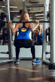Young blond woman lifting barbells in the gym. royalty free stock photos