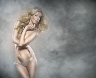 A young blond woman in lingerie on a foggy background Stock Image