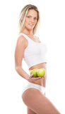A young blond woman in lingerie holding apples Stock Photos