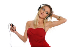 Young blond woman listening to music. Young blond woman wearing headphones listening to music isolated on a white background Stock Images