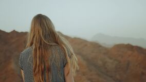 Young blond woman in long dress walks on top of mountain. Mountain landscape with sunset, slow motion, full hd