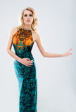 Young blond woman in a long fashion dress. Young and beautiful model girl posing in studio in fashion summer dress Stock Photos