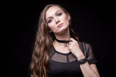 Young blond woman with long hair and choker. On black background Royalty Free Stock Image