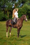 Young blond woman with long hair jockey rider jumping on a bay horse. On a background of field and forest royalty free stock photography