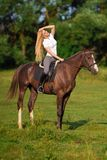 Young blond woman with long hair jockey rider jumping on a bay horse. On a background of field and forest royalty free stock image