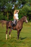 Young blond woman with long hair jockey rider jumping on a bay horse. On a background of field and forest royalty free stock photos