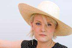 Somber Woman in Hat. Young. blond woman looking at camera with sober expression, wearing wide-brim straw hat Royalty Free Stock Photos