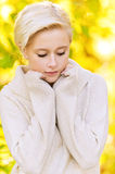 Young blond woman looking somewhere. Portrait of young beautiful blond woman wearing beige sweater and looking somewhere at park Royalty Free Stock Photography
