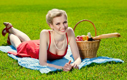 Young blond woman is lying on grass Royalty Free Stock Image