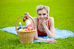 Young blond woman is lying on grass Stock Photos