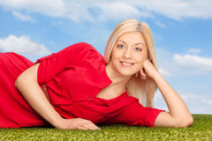 Young blond woman lying on a grass. In a field outdoors with the sky and clouds in the background royalty free stock photo