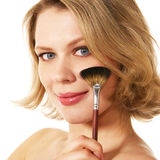 Young blond woman with make-up brush Royalty Free Stock Photography