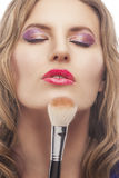Young blond woman with make-up brush Stock Photography