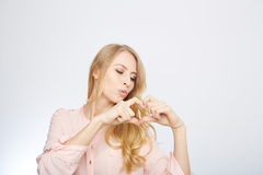 Young blond woman making a heart symbol Stock Photography