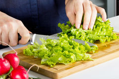 Young blond woman making salad in kitchen Royalty Free Stock Photos