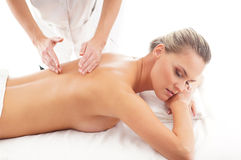A young blond woman on a massage procedure Stock Images