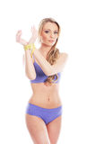 A young blond woman with a measuring tape Royalty Free Stock Images