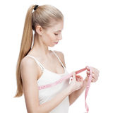Young blond woman measuring waist Royalty Free Stock Images