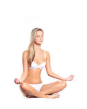A young blond woman meditating in white lingerie Stock Images