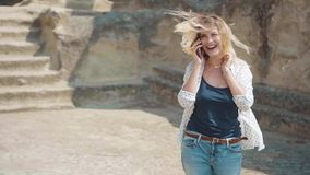 A young blond woman with natural beauty speaks on a mobile phone with friends and family at the edge of the world. A. Happy face with a smile, positive emotions stock footage