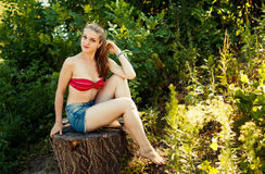 Young blond woman at nature, sitting on stump Royalty Free Stock Photography