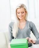 Young blond woman opening a box Royalty Free Stock Photography