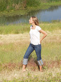 Young blond woman outdoors in grass with water. Outdoors shot of blond woman in white top and jeans Royalty Free Stock Photos