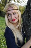A young blond woman in the park. Near the tree. Thinking Stock Photos