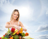 A young blond woman and a pile of fresh fruits Stock Image