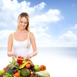 A young blond woman and a pile of fresh fruits Stock Photo