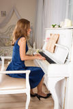 Young blond woman playing the piano Royalty Free Stock Image
