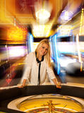 Young blond woman playing roulette in casino and winning Stock Images