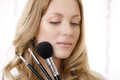 Young blond woman portrait with makeup brushes Royalty Free Stock Photos