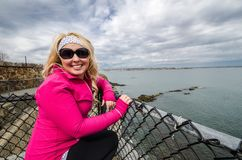 Young blond woman poses and enjoys the scenery along the Cliff Walk in Newport Rhode Island. Overcast day near chain link fence royalty free stock photo