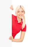 Young blond woman posing behind a blank panel Stock Photography