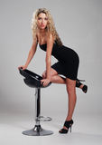 A young blond woman posing in a black dress Stock Image