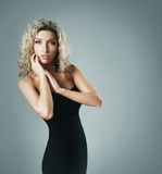 A young blond woman posing in a black dress Stock Photo