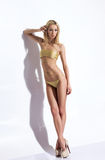 A young blond woman posing in a golden swimsuit Royalty Free Stock Photo
