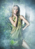 A young blond woman posing in a green forest Royalty Free Stock Photos