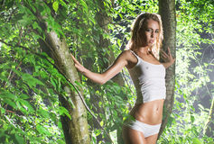 A young blond woman posing in a green forest Royalty Free Stock Image