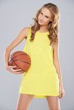 Young blond woman posing and holding basket ball Royalty Free Stock Photos