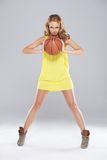 Young blond woman posing and holding basket ball Royalty Free Stock Photo