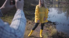 Portrait young blond woman posing near forest with lake. Man making photo of her by mobile phone. Young blond woman posing near forest with lake in yellow coat stock footage