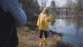 Young blond woman posing near forest with lake. Man making photo of her by mobile phone. Young blond woman posing near forest with lake in yellow coat and stock video footage