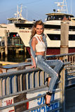 Young blond woman  posing on a pier with ship on the background. Fashion look. Royalty Free Stock Images