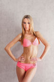 A young blond woman posing in a pink swimsuit Royalty Free Stock Photography