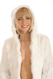 A young blond woman posing in a warm fur hoodie. A young and attractive blond Caucasian woman posing in a warm fur hoodie. The image is isolated on a white Royalty Free Stock Image