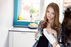 Young blond woman pouring milk stock photos