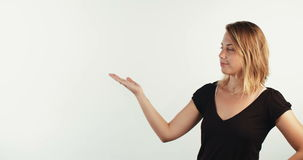 Young blond woman presenting some information on a white background stock video
