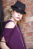 A young blond woman with purple shirt and black hat. Royalty Free Stock Photography